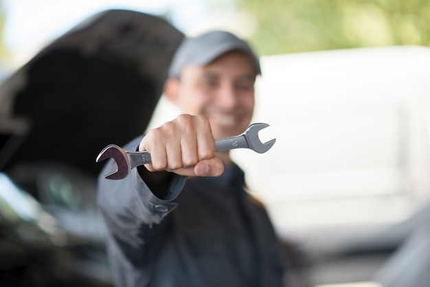 Smiling mechanic holding a wrench