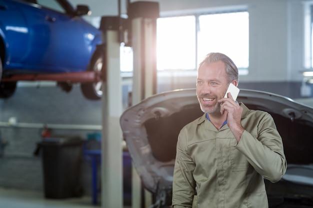 Meccanico sorridente parlare su un telefono cellulare