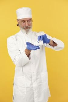 Sorridente medico con le pillole. isolato. uomo in guanti blu.