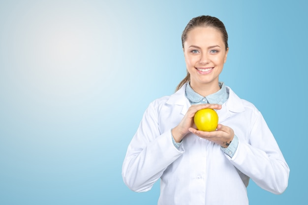 Smiling medical doctor woman with apple
