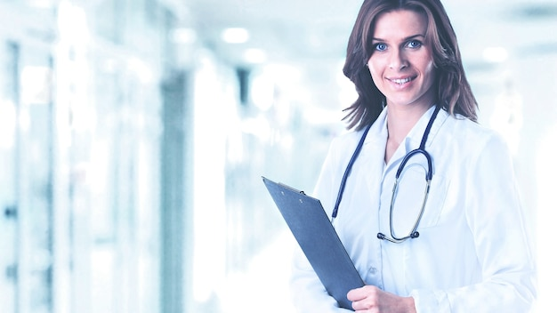 Smiling medical doctor woman with a folder in hospital on background of bright hall