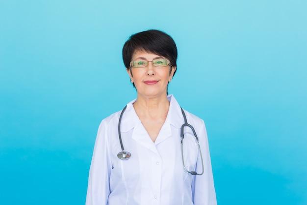 聴診器で笑顔の医師の女性。コピースペースと青い背景の上