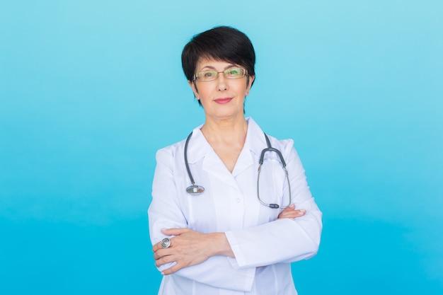 聴診器で笑顔の医師の女性。青い背景の上