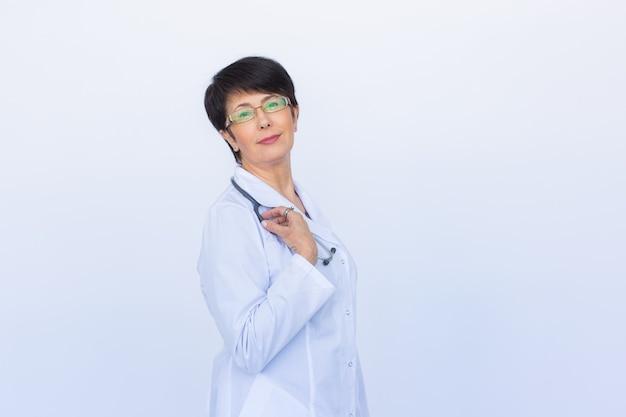 聴診器で笑顔の医師の女性。白い壁の上。