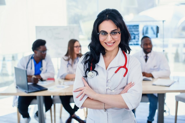 Smiling medical doctor woman with stethoscope standing in front of medic team at hospital. attractive young female doctor in white coat and glasses