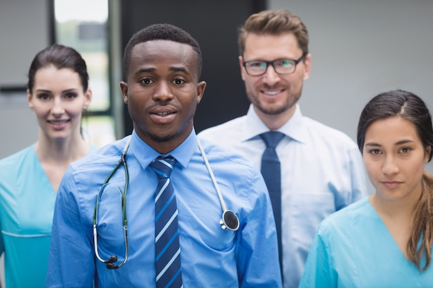 Smiling medical team standing together in hospital corridor