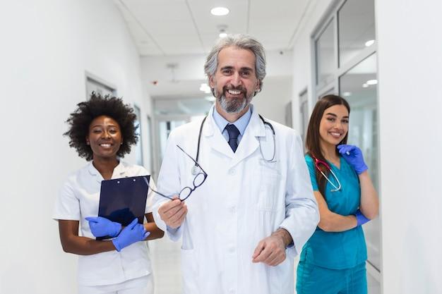 病院、職業で一緒に立っている笑顔の医療チーム