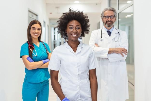 病院で一緒に立っている笑顔の医療チーム