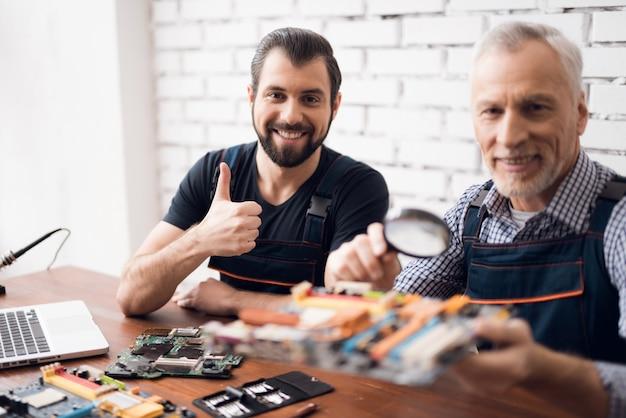 Улыбающиеся мужчины делают ремонт устройства обслуживания ноутбука.