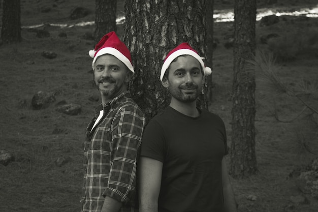 Smiling men posing with red christmas hats by pine tree trunk on forest park happy gay couple