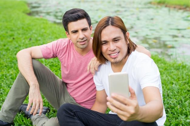 공원에서 스마트 폰 selfie를 복용 웃는 남자