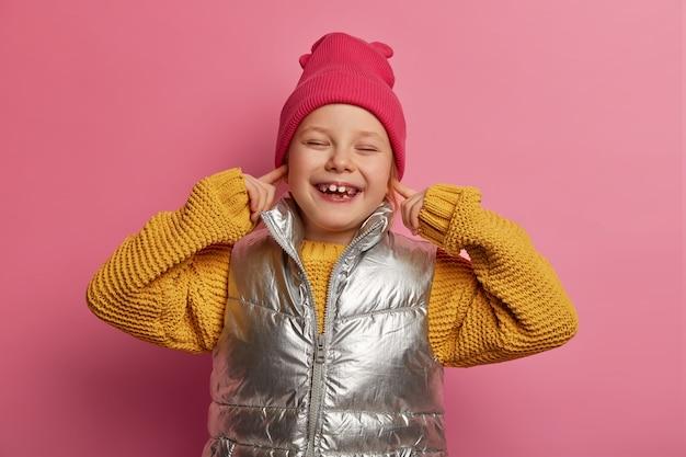 Sorridente bambino allegro tappi le orecchie con le dita anteriori, non vuole sentire i vicini rumorosi, indossa cappello, maglione lavorato a maglia e gilet, evita il suono forte, sorride ampiamente, mostra i denti isolati sul muro rosa