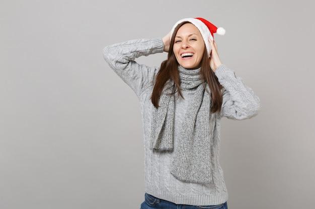 灰色のセータースカーフクリスマス帽子の笑顔のメリーサンタの女の子は、灰色の背景、スタジオの肖像画に分離された頭に手を置きます。明けましておめでとうございます2019お祝いホリデーパーティーのコンセプト。コピースペースをモックアップします。