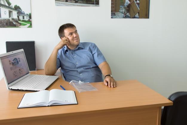 노트북과 메모가 있는 테이블 공간에서 웃고 있는 중년 남성 기업가가 뭔가 생각하면서 올려다보고 있습니다.