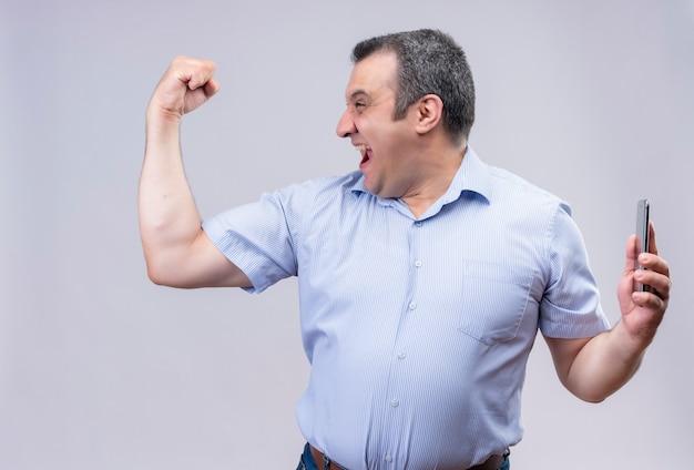 Улыбающийся мужчина среднего возраста в синей полосатой рубашке с поднятой рукой, сгибающий бицепс, держа мобильный телефон, стоя на белом фоне