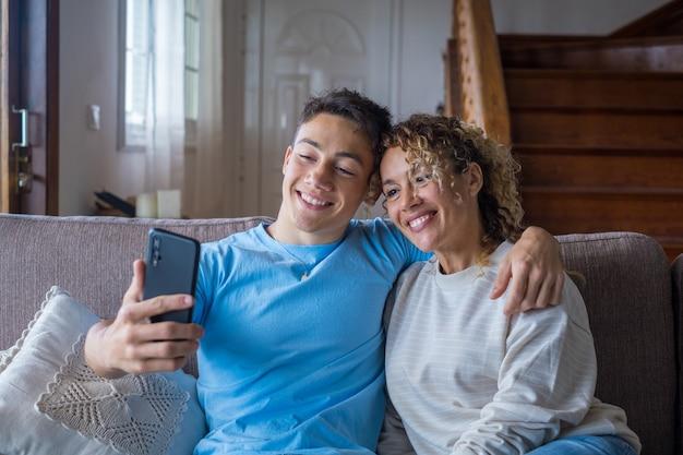 Улыбающаяся мать среднего возраста 40 лет отдыхает со взрослым сыном, использующим смартфон вместе, счастливый молодой человек наслаждается семейными выходными с мамой, делающей селфи, веселится дома