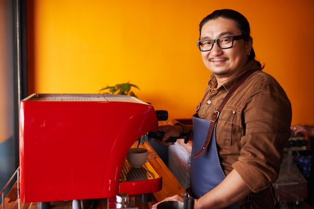 Smiling middle-aged asian man in apron standing next to espresso machine and smiling
