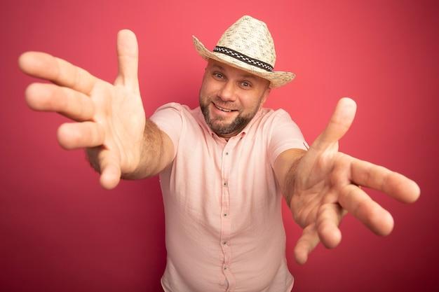 분홍색 티셔츠와 분홍색에 고립 된 손을 올리는 모자를 쓰고 웃는 중년 대머리 남자