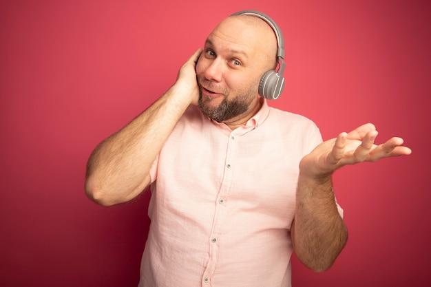 분홍색 티셔츠와 손을 확산 헤드폰을 입고 웃는 중년 대머리 남자