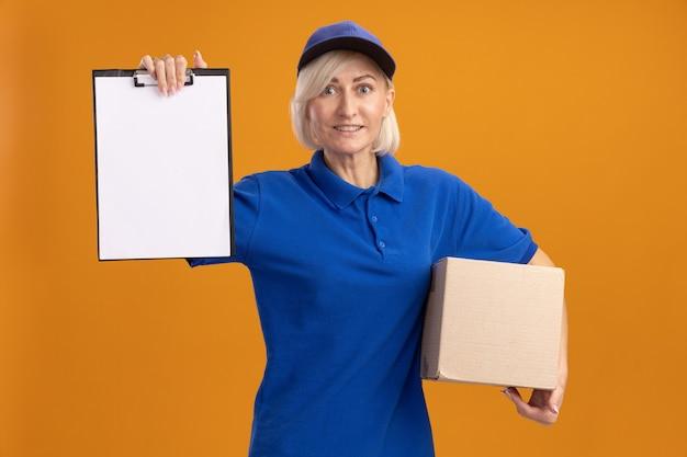 Sorridente bionda di mezza età donna di consegna in uniforme blu e cappuccio che tiene scatola di cartone e mostra appunti isolati su parete arancione