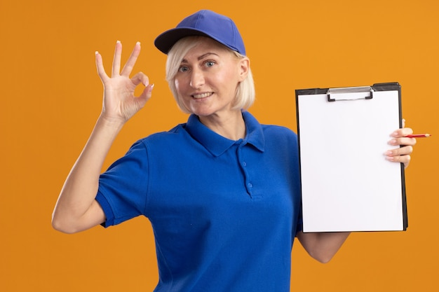 Smiling middle-aged blonde delivery woman in blue uniform and cap showing clipboard to camera  doing ok sign isolated on orange wall
