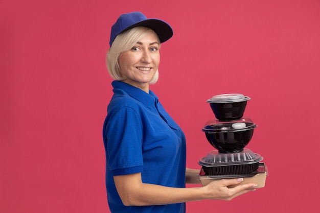 Smiling middle-aged blonde delivery woman in blue uniform and cap standing in profile view holding paper food package and food containers  isolated on pink wall with copy space