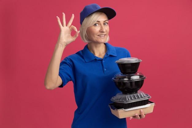 Улыбающаяся блондинка среднего возраста доставляющая товары в синей униформе и кепке держит бумажный пакет с едой и пищевые контейнеры, делающие знак ок, изолированные на розовой стене