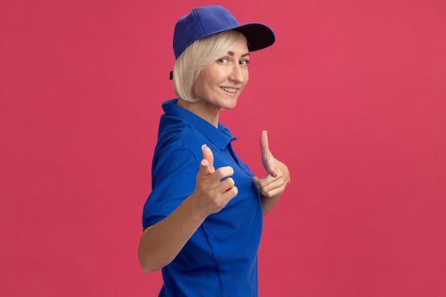파란색 유니폼을 입고 프로필 보기에 모자를 쓰고 웃고 있는 중년 금발 배달 여성이 복사 공간이 있는 분홍색 벽에 격리된 제스처를 하고 있습니다.