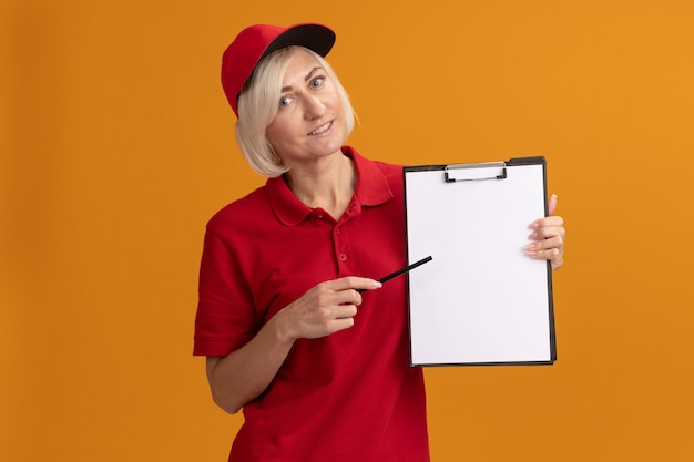 赤い制服とコピースペースでオレンジ色の壁に分離された鉛筆でクリップボードを指しているキャップで笑顔の中年金髪配達女性