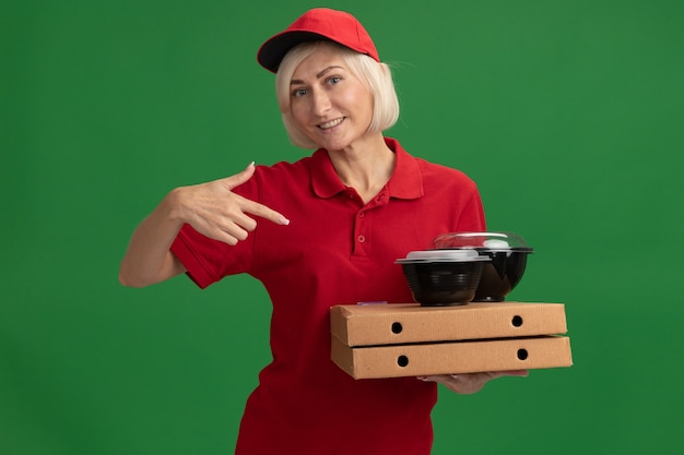 Smiling middle-aged blonde delivery woman in red uniform and cap holding and pointing at pizza packages with food containers on them  isolated on green wall