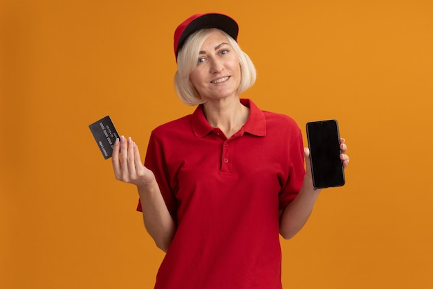 Smiling middle-aged blonde delivery woman in red uniform and cap looking at front holding credit card and mobile phone isolated on orange wall