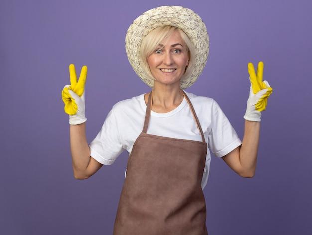平和のサインをしている帽子とガーデニング手袋を身に着けている制服を着た中年の金髪の庭師の女性の笑顔