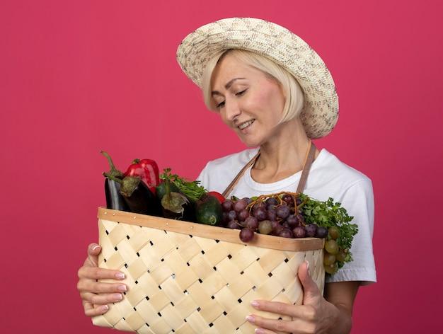 Улыбающаяся белокурая женщина-садовник средних лет в униформе в шляпе держит и смотрит на корзину овощей, изолированную на малиновой стене