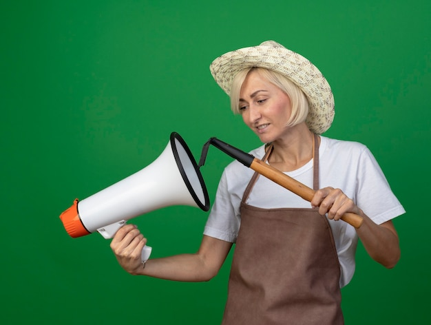 緑の壁に隔離されたその近くの熊手を保持し、スピーカーを保持し、帽子をかぶって制服を着た中年の金髪の庭師の女性の笑顔