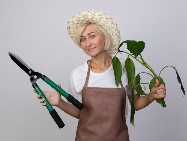 Улыбающаяся блондинка-садовник средних лет в униформе в шляпе держит ножницы для растений и изгороди, изолированные на белой стене