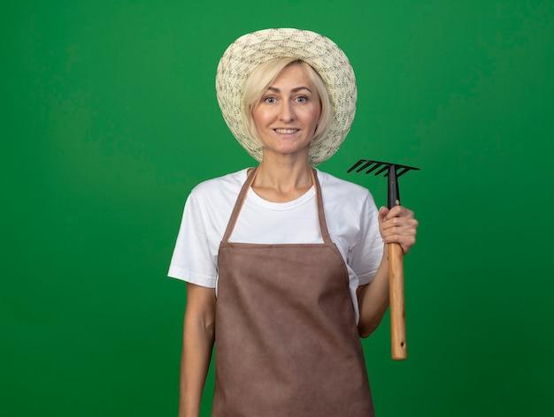 복사 공간이 있는 녹색 벽에 격리된 앞을 바라보는 갈퀴를 들고 모자를 쓰고 제복을 입은 중년 금발 정원사 여성