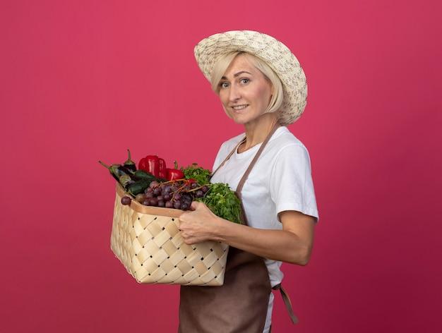 Улыбающаяся белокурая женщина-садовник средних лет в униформе в шляпе, стоящая в профиль и держащая корзину с овощами, смотрящую вперед, изолированную на малиновой стене