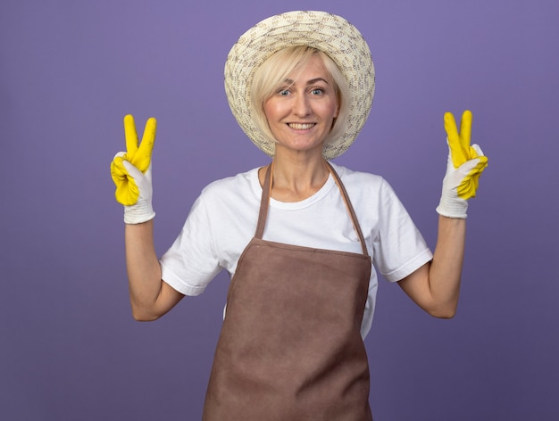 Smiling middle-aged blonde gardener woman in uniform wearing hat and gardening gloves doing peace sign