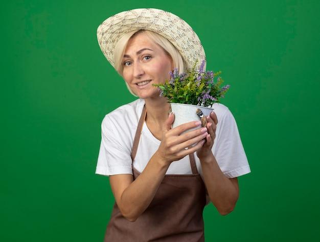 Sorridente giardiniere bionda di mezza età donna in uniforme che indossa un cappello che tiene vaso di fiori