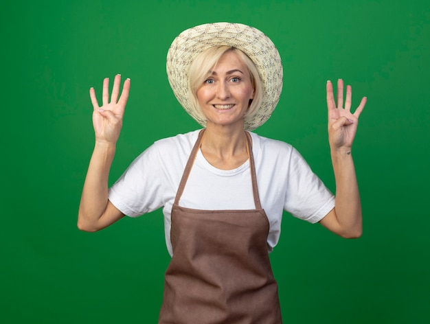 Sorridente giardiniere bionda di mezza età donna in uniforme che indossa un cappello che mostra otto con le mani isolate sul muro verde