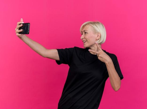 真っ赤な背景で隔離のselfieを取るピースサインをしている笑顔の中年金髪スラブ女性