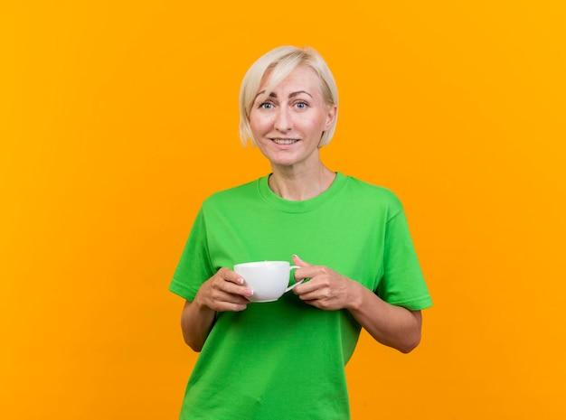 Улыбающаяся белокурая славянская женщина средних лет, держащая чашку чая, смотрит вперед, изолированную на желтой стене с копией пространства