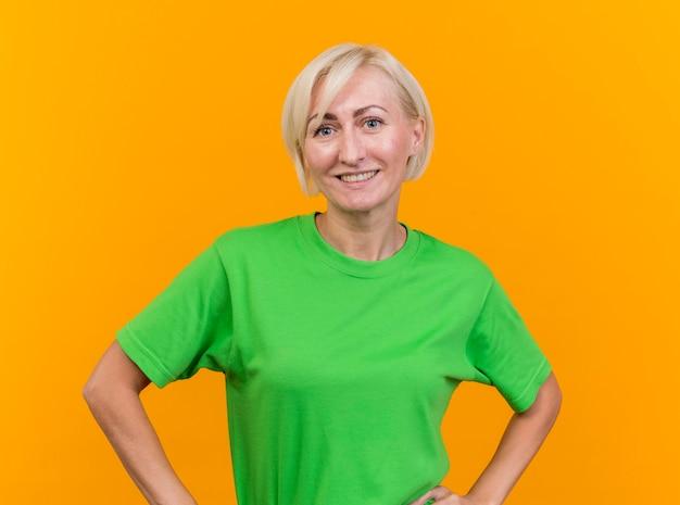 Sorridente donna slava bionda di mezza età che guarda l'obbiettivo tenendo le mani sulla vita isolato su sfondo giallo