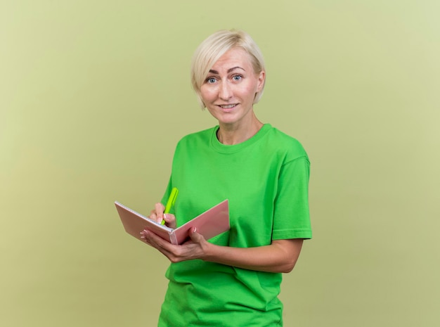 Smiling middle-aged blonde slavic woman looking at front holding pen and note pad looking at camera isolated on olive green wall with copy space
