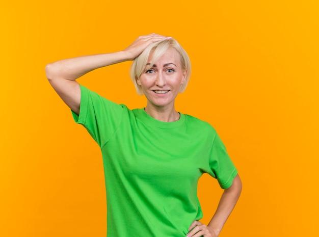 Sorridente donna slava bionda di mezza età guardando davanti mettendo la mano sulla testa tenendone un altro in vita isolato sulla parete gialla con lo spazio della copia