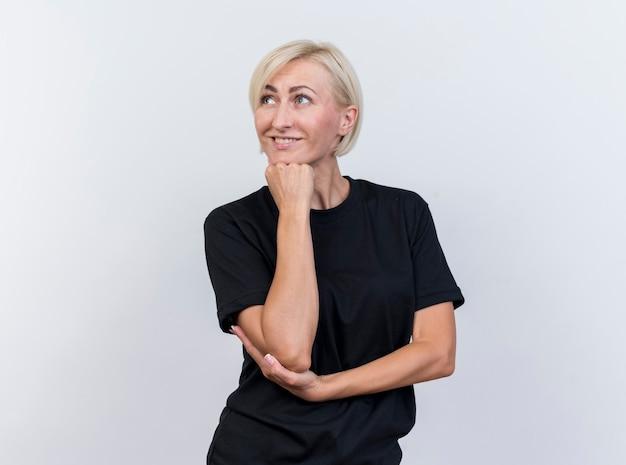 Улыбающаяся белокурая славянская женщина средних лет, положив руку на локоть и подбородок, глядя в сторону, изолированную на белом фоне с копией пространства
