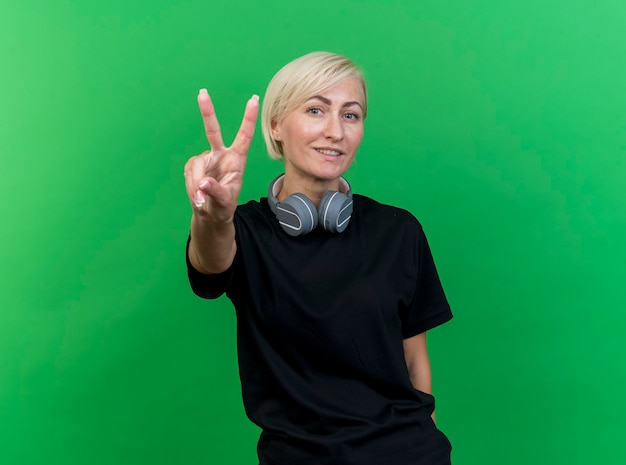 복사 공간이 녹색 배경에 고립 된 평화 서명을하고 카메라를보고 목에 헤드폰을 착용 중년 금발 슬라브 여자 미소