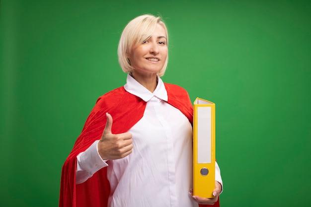 コピースペースと緑の壁に分離された親指を示す赤い岬の保持フォルダーで笑顔の中年金髪のスーパーヒーローの女性