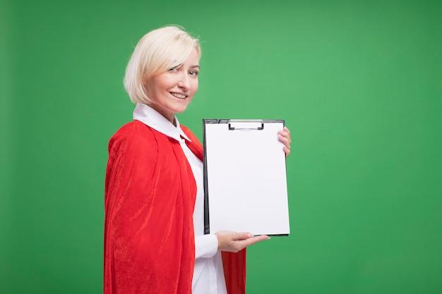 빨간 망토를 입은 웃는 중년 금발 슈퍼히어로 여성이 복사공간이 있는 녹색 벽에 격리된 전면에 클립보드를 보여주는 프로필 보기에 서 있습니다.