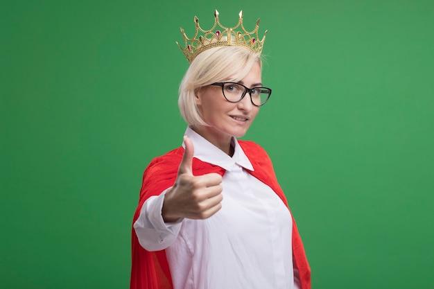 Sorridente donna di mezza età bionda supereroe in mantello rosso con gli occhiali e corona che mostra pollice in su isolato sulla parete verde con spazio di copia